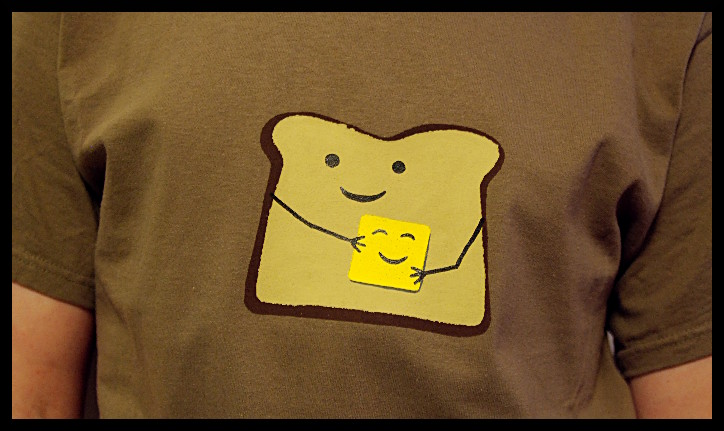 Brown shirt with a cartoon piece of toast smiling, hugging a pat of butter, also smiling.
